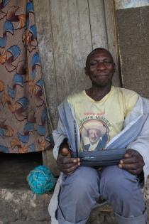 En mand sidder her udenfor et hus i Kisoro og lytter radio. T-shirten er printet med et billede af Ugandas president, Yoweri Museveni, som kaldes M7 i daglig tale. Foto af Lisbeth Kristine Olesen